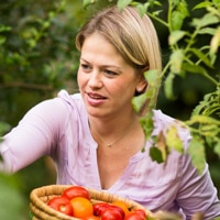 A blonde woman picking tomatoes