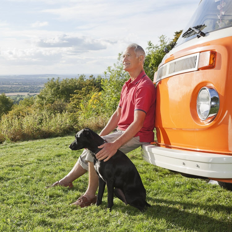 Man with dog sitting on orange van