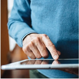 A man's finger touching a tablet device