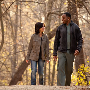 Couple going for a walk on a wooded park trail
